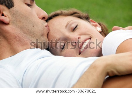 smiling woman with eyes closed resting her head on her husband's chest as he kisses her forehead - stock photo