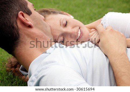 smiling woman with eyes closed resting her head on her lover's chest as he kisses her forehead as they hold hands - stock photo