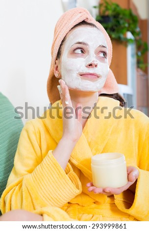 Smiling woman with face pack relaxing on sofa indoors