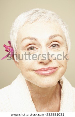 Smiling Woman with Fresh Flower Behind Her Ear - stock photo
