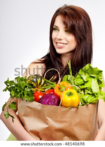 Smiling woman with fruits and vegetables. Over white background