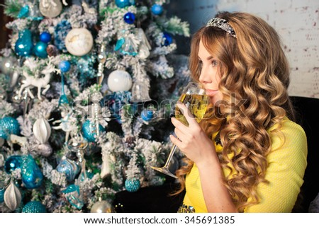 smiling woman with glass of champagne with christmas tree on background - stock photo