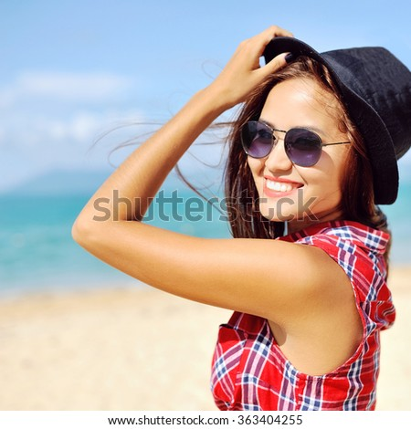 Smiling woman with hat and sunglasses in summertime