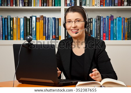 Smiling woman with headphone, computer and webcam in her office, consultant, adviser, teacher, online learning, business - stock photo