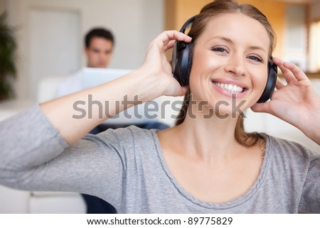 Smiling woman with headphones on with man sitting behind her on the sofa - stock photo