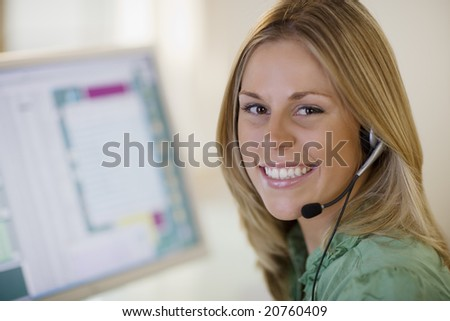 Smiling woman with headset and computer monitor - stock photo