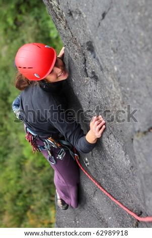 Smiling woman with helmet climbing basalt rock - stock photo