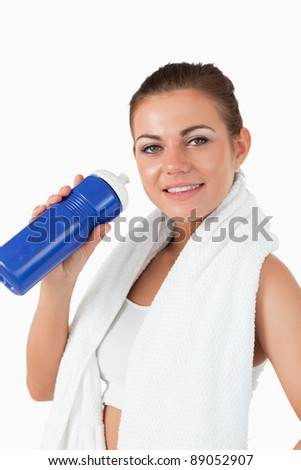 Smiling woman with her bottle after workout against a white background