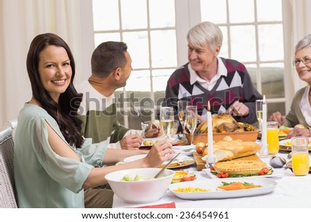 Smiling woman with her family during christmas dinner at home in the living room - stock photo