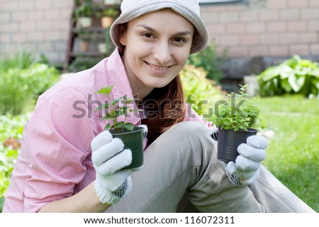 Smiling woman with herbs in garden - stock photo