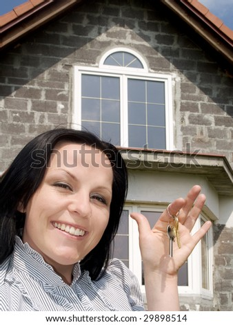 smiling woman with keys to the new house - stock photo