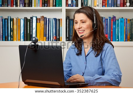Smiling woman with laptop, camera and headset video telephoning via the internet, skype - stock photo