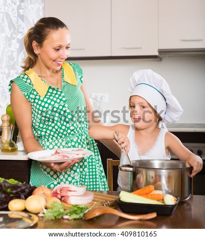 Smiling woman with little daughter in cook hat cooking at home kitchen - stock photo