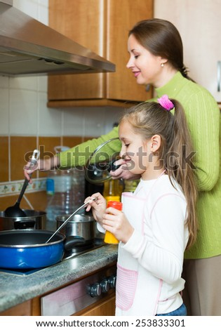 Smiling woman with little daughter preparing soup together at domestic kitchen. Focus on girl