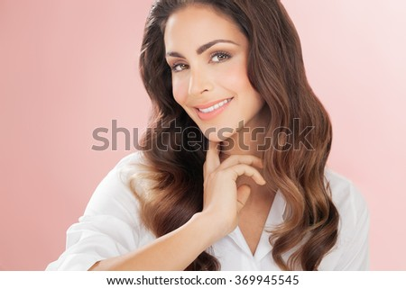 Smiling woman with long hair over delicate romantic pink background. Fashion and beauty concept in studio.