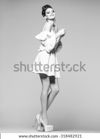 smiling woman with long legs in white dress, fur and high-heels posing in the studio