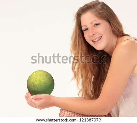 Smiling woman with long wavy blond hair wearing a smock top, holding green orb - stock photo