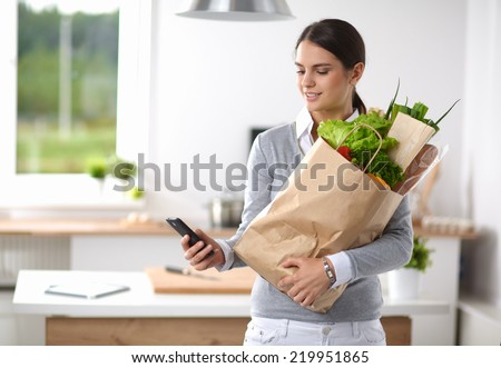 Smiling woman with mobile phone holding shopping bag in kitchen - stock photo