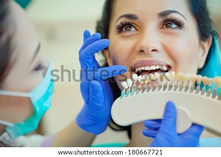 smiling woman with palette for tooth color - stock photo
