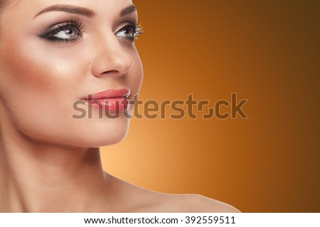 Smiling woman with perfect skin and make up over brown background. Beauty and spa. Welness and naturality - stock photo