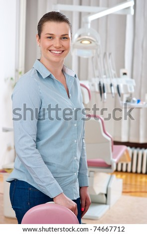 smiling woman with perfect white teeth in dentist office - stock photo