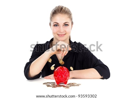 Smiling woman with red piggy bank and falling coins - stock photo