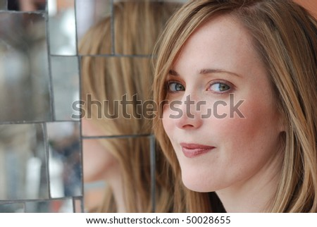 smiling woman with reflection in mirrors - stock photo