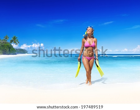 Smiling woman with scuba gear on a tropical beach. - stock photo