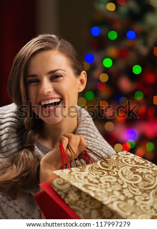 Smiling woman with shopping bag in front of Christmas lights - stock photo