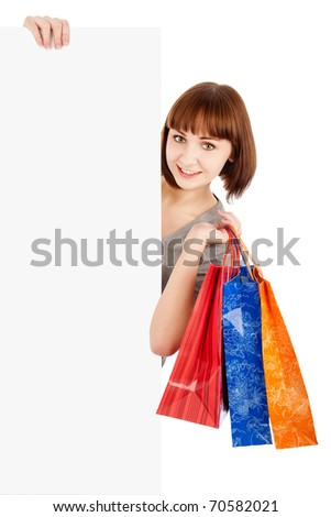 Smiling woman with shopping bags holding blank billboard sign, isolated on white - stock photo