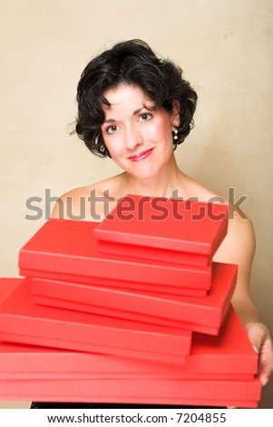 Smiling woman with short curly hair, holding a stack of red gift boxes - stock photo