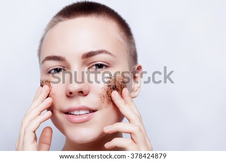 Smiling woman with short hair, bald cleans the skin coffee skrub, studio shot, close-up portrait - stock photo