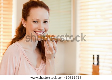 Smiling woman with slice of bread in her hand - stock photo