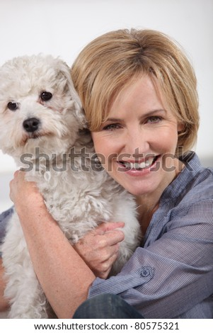 Smiling woman with small white dog - stock photo