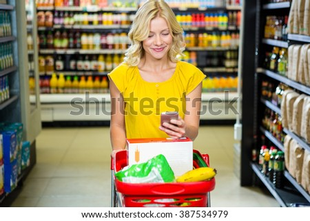 Smiling woman with smartphone pushing trolley in aisle at supermarket - stock photo