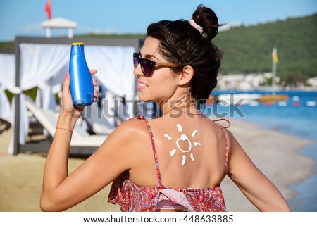 smiling woman with sun-shaped sun cream.Sun Drawn On Woman's Shoulder With Sun Protection Cream - stock photo
