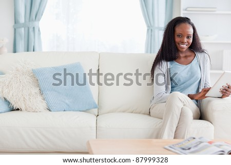 Smiling woman with tablet on sofa - stock photo