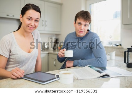 Smiling woman with tablet pc and man with newspaper drinking coffee in kitchen - stock photo