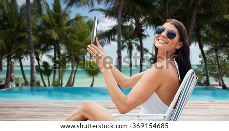 smiling woman with tablet pc sunbathing on beach