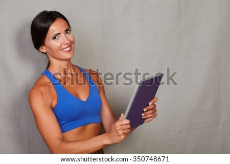 Smiling woman with toothy smile holding tablet and looking at camera against grey texture background - stock photo