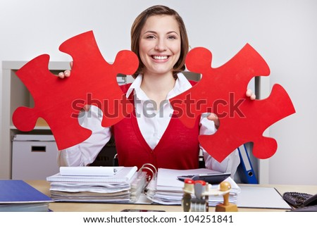 Smiling woman with two oversized red jigsaw puzzle pieces - stock photo