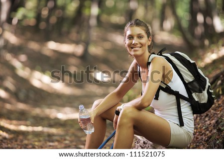 Smiling woman with walking sticks in a forest, having a break - stock photo