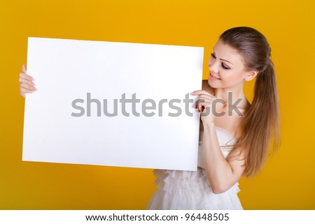 Smiling woman with white blank on yellow background - stock photo