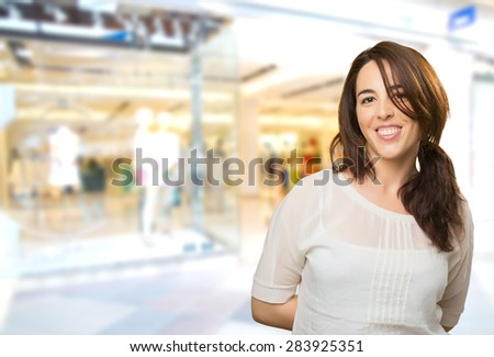 Smiling woman with white shirt. Over shopping center background