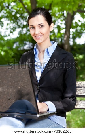 smiling woman working on laptop in spring park - stock photo