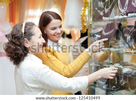 Smiling women  chooses bridal accessories at store of wedding fashion - stock photo