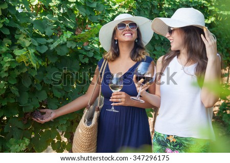 Smiling women drinking wine and looking at grapes in vineyard. Two girls with wineglasses walking in vineyard and laughing. - stock photo