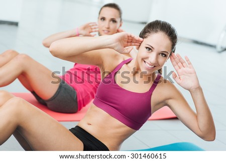 Smiling women exercising at gym on a mat and looking at camera, fitness and workout concept - stock photo