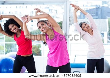 Smiling women exercising with arms raised in fitness studio - stock photo