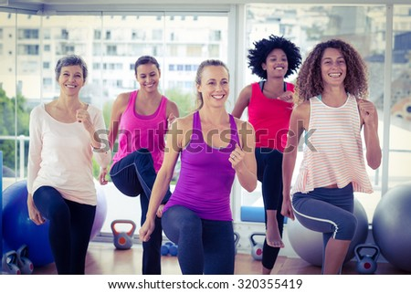 Smiling women exercising with clasped hands in fitness studio - stock photo